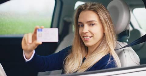 vrouw laat rijbewijs zien terwijl ze in de auto zit